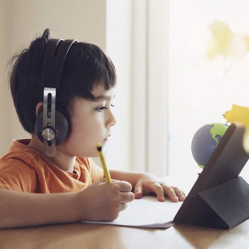 Portrait of preschool kid using tablet for his homework, Soft focus of Child wearing head phone doing homework by using digital tablet searching information on internet, Home schooling education concept,self isolation or Social Distancing